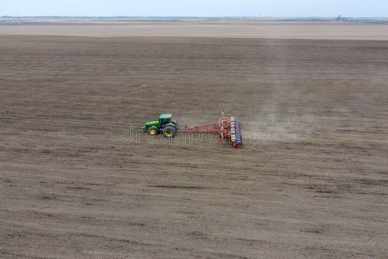 Het zaaien van graan Tractor met een zaaimachine op het gebied royalty-vrije stock fotografie