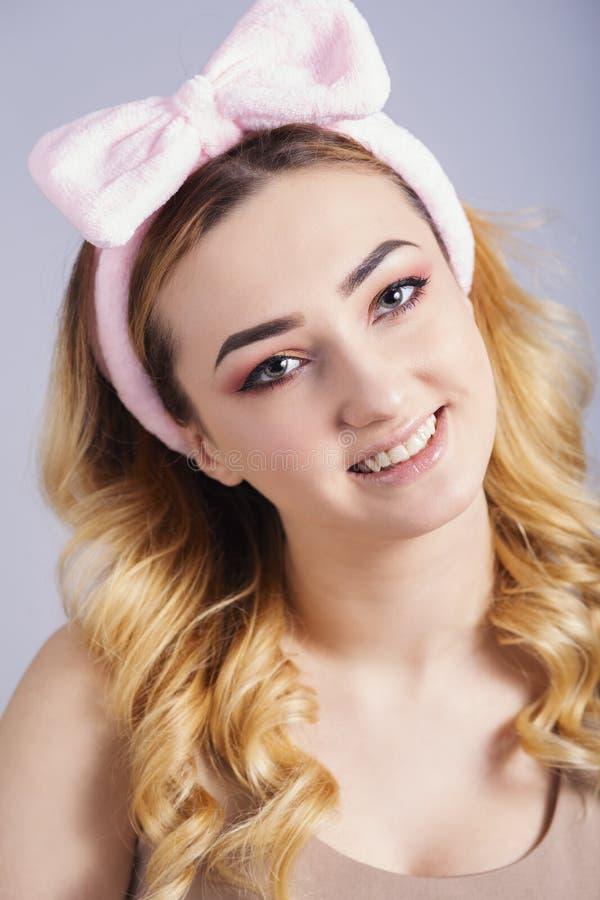 Het zachte studioportret van een gelukkige jonge vrouw met pluizige hoepel op hoofd, vers meisjesgezicht met maakt omhoog, royalty-vrije stock foto's