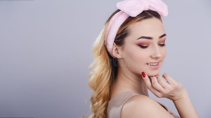 Het zachte studioportret van een mooie jonge vrouw met pluizige zachte hoepel op hoofd dat haar plukt, vers meisjesgezicht met ma stock foto's