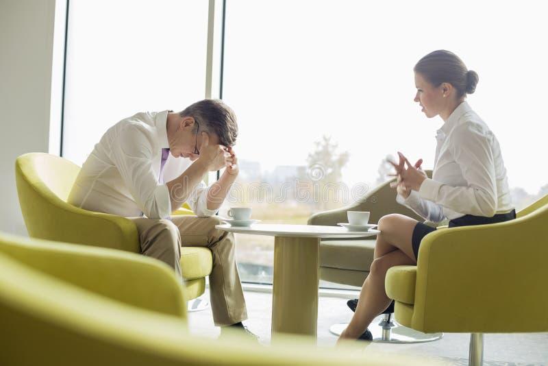 Het zakenlui in ernstige bespreking op kantoor lobbyt royalty-vrije stock afbeelding