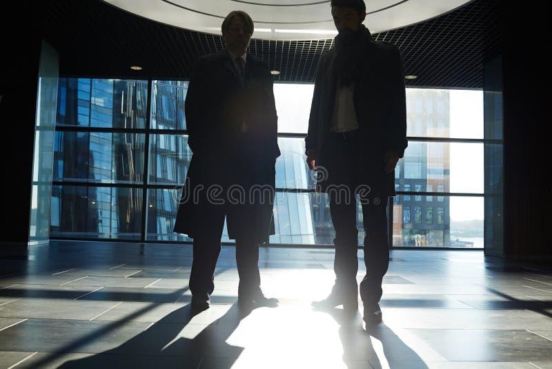 Het zakenlui in Schemerig Bureau lobbyt stock foto's