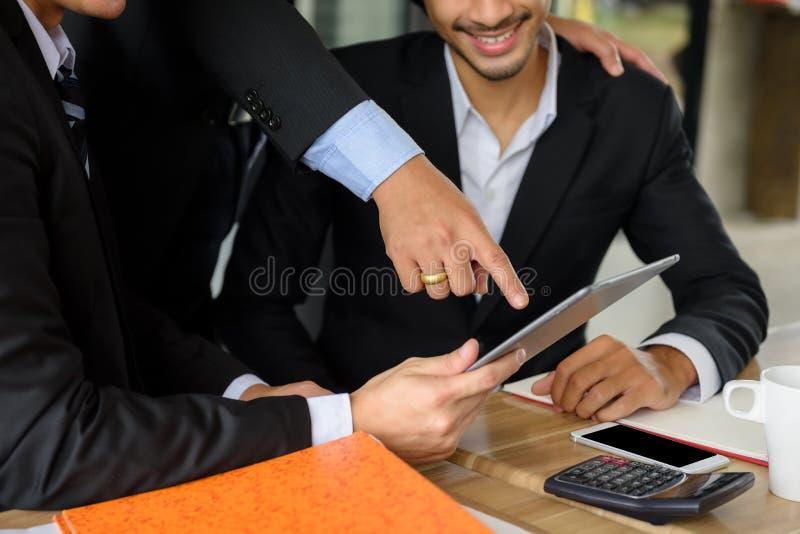 het zakenmanteam bespreekt plan door tablet stock afbeelding