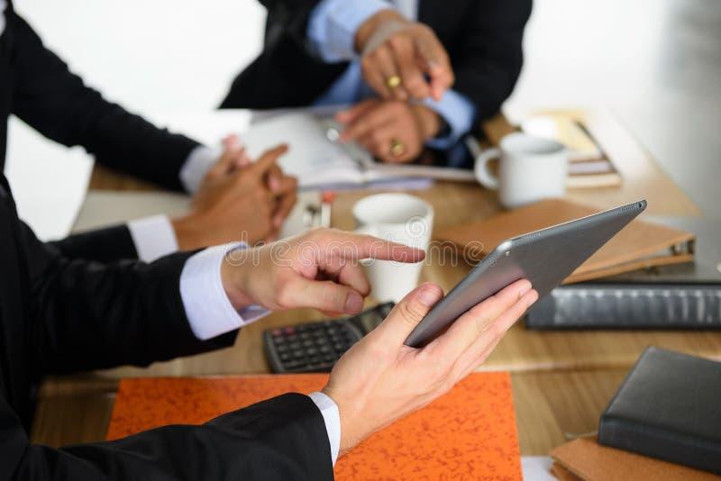 Het zakenmanteam bespreekt project gebruikend tablet stock afbeelding