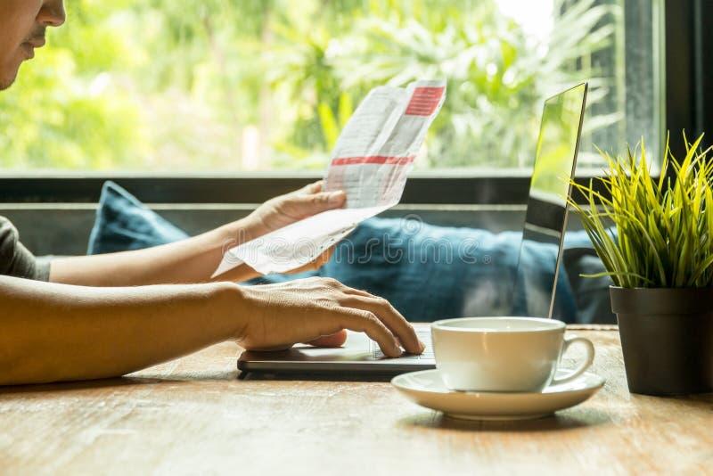 Het zakenmanwerk aangaande laptop die rekening met koffie controleren op houten lijst stock afbeelding