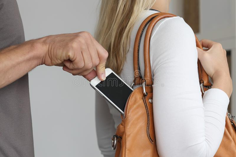 Het zakkenrollen van een mobiele telefoon uit de handtas van een vrouw royalty-vrije stock fotografie