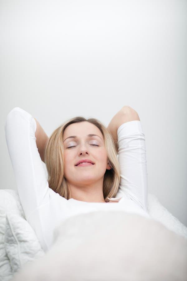 Het zalige jonge vrouw ontspannen in bed royalty-vrije stock afbeelding