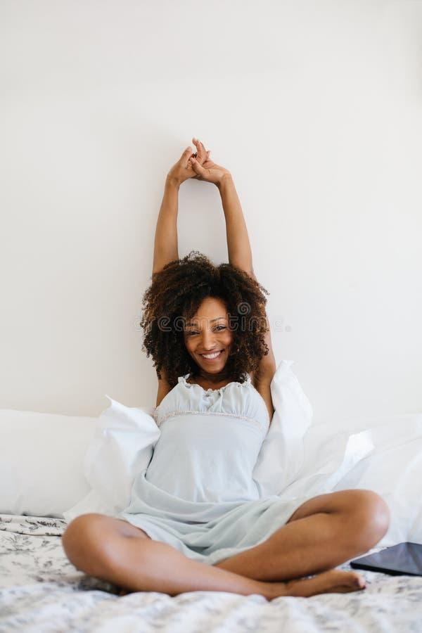 Het zalige vrouw ontspannen in haar bed thuis stock foto's