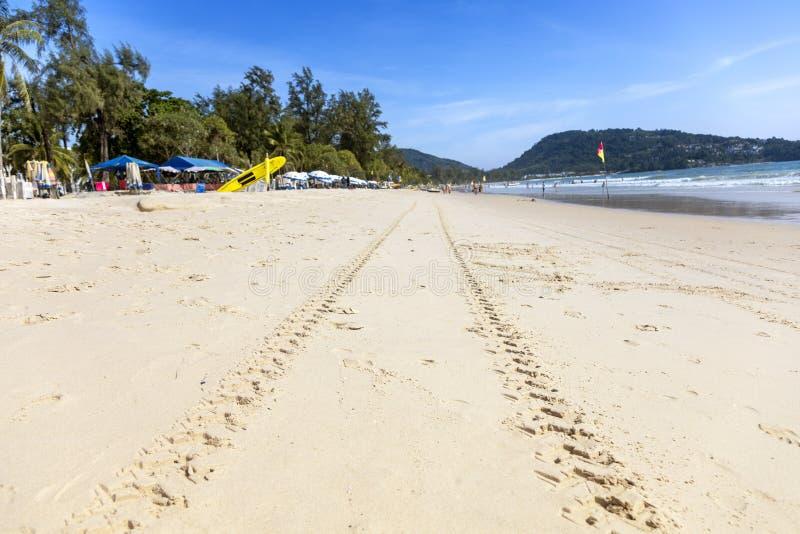 Het zand op het strand met duidelijke hemel moutain en de mensen spelen wateroverzees royalty-vrije stock fotografie