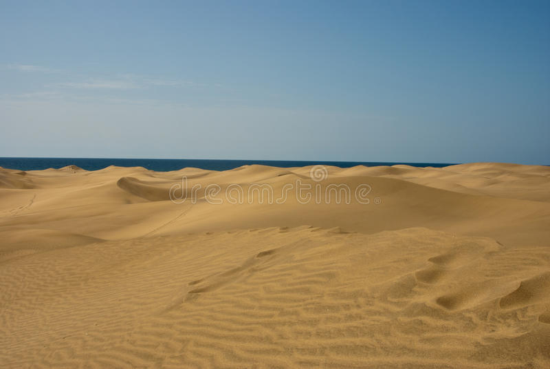 Het zandduinen van golven in woestijn met overzees stock afbeeldingen