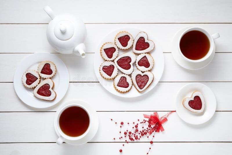 Het zandkoekhart vormde koekjes voor Valentijnskaartendag met theepot en twee kop theeën op witte houten achtergrond gebakken royalty-vrije stock afbeelding