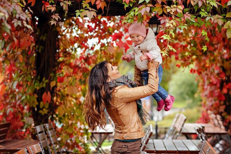 Het zeer charmante mooie donkerbruine mamma in een bruin jasje werpt omhoog stock foto