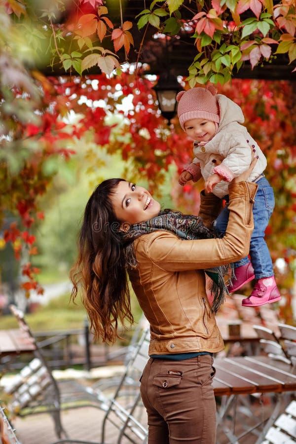 Het zeer charmante mooie donkerbruine mamma in een bruin jasje werpt omhoog stock foto's