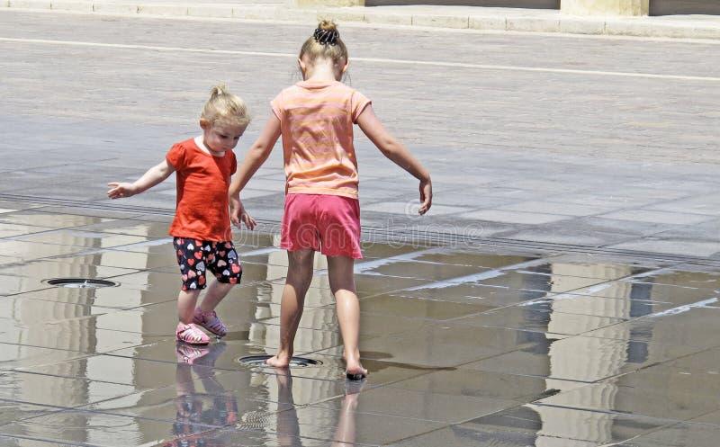 Het is zeer heet en twee kinderen die in de fontein in het vierkant spelen stock afbeeldingen
