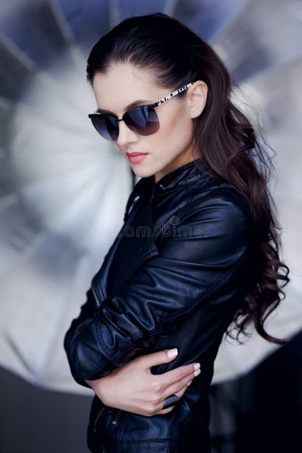 Het zekere en sexy jonge donkerbruine vrouw stellen in zwarte leerjasje en zonnebril, op een creave zilveren achtergrond stock foto's