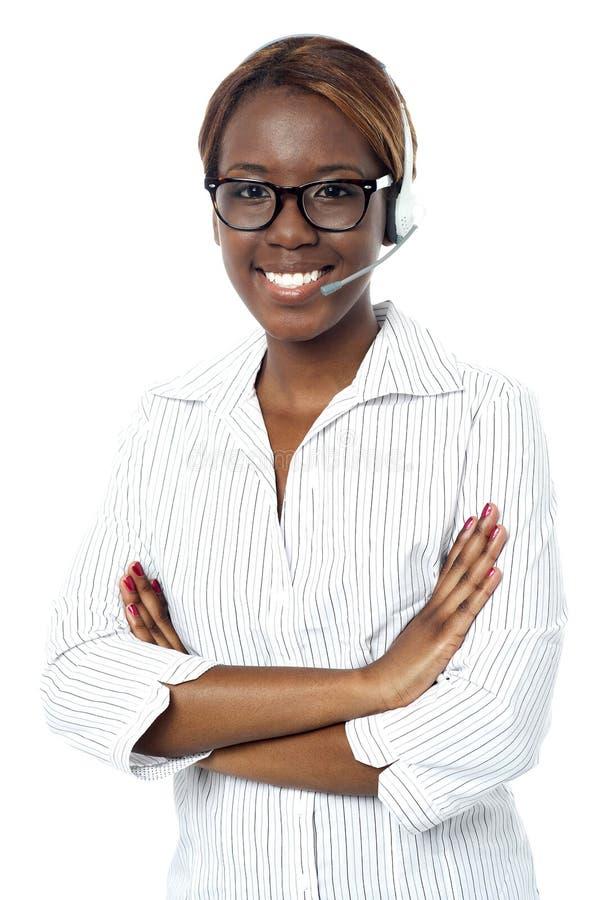 Het zekere exploitantdame glimlachen, die hoofdtelefoon draagt stock afbeelding