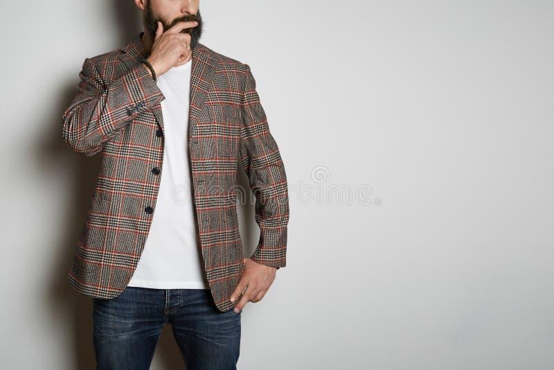 Het zekere gebaarde zakenmanmodel stelt in toevallig jasje en leeg wit de zomerkatoen van de t-shirtpremie, op wit royalty-vrije stock afbeelding