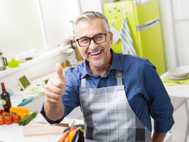 Het zekere het glimlachen mens stellen in zijn keuken royalty-vrije stock foto's