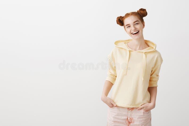 Het zekere heldere meisje met twee modieuze uitrusting dragen en broodjeskapsel die dient zakken in, ruim glimlachend houden stock foto's