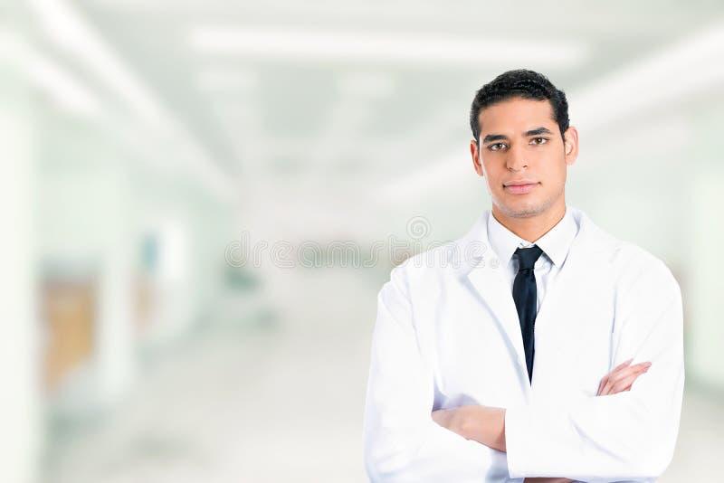 Het zekere mannelijke arts glimlachen bewapent gevouwen status in het ziekenhuis royalty-vrije stock foto