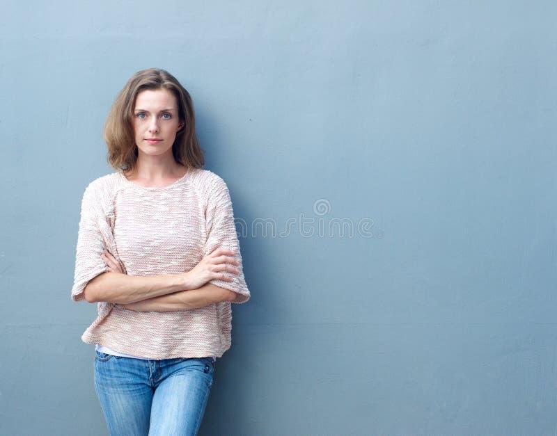 Het zekere medio volwassen vrouw stellen met gekruiste wapens stock foto's