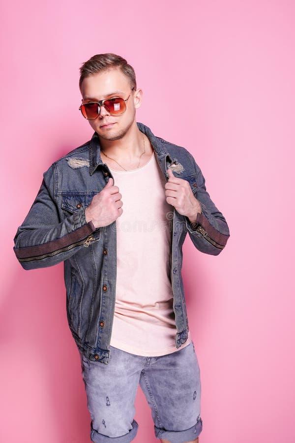 Het zekere modieuze toevallige kerel stellen op roze royalty-vrije stock fotografie
