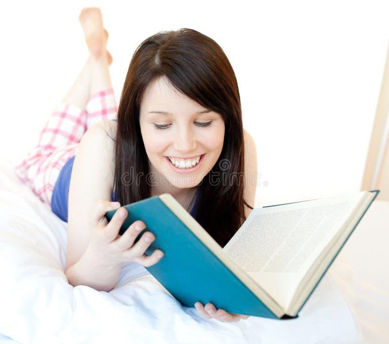 Het zekere tienermeisje bestuderen die op een bed ligt royalty-vrije stock afbeeldingen