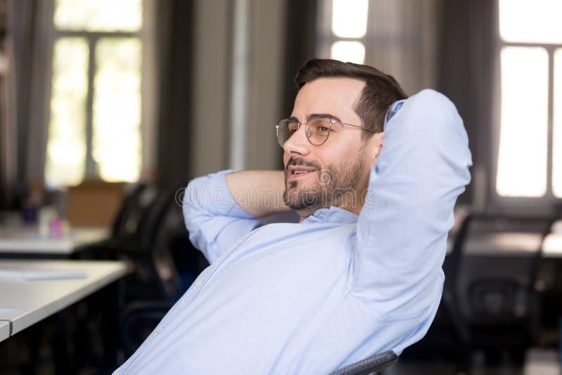 Het zekere zakenman ontspannen die terug op het werk leunen royalty-vrije stock foto