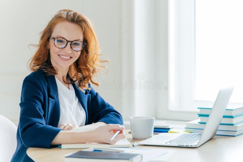 Het zelf zekere jonge vrouwelijke het werkproces van directeursplannen, schrijft hoofdtheses in blocnote, herschrijft informatie  stock foto's