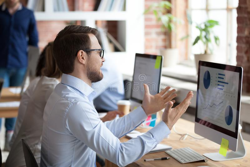 Het zenuwachtige mannelijke werknemer gesturing boos over computerprobleem royalty-vrije stock fotografie
