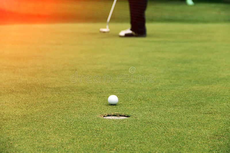 Het zetten van golfspelers op green stock foto's