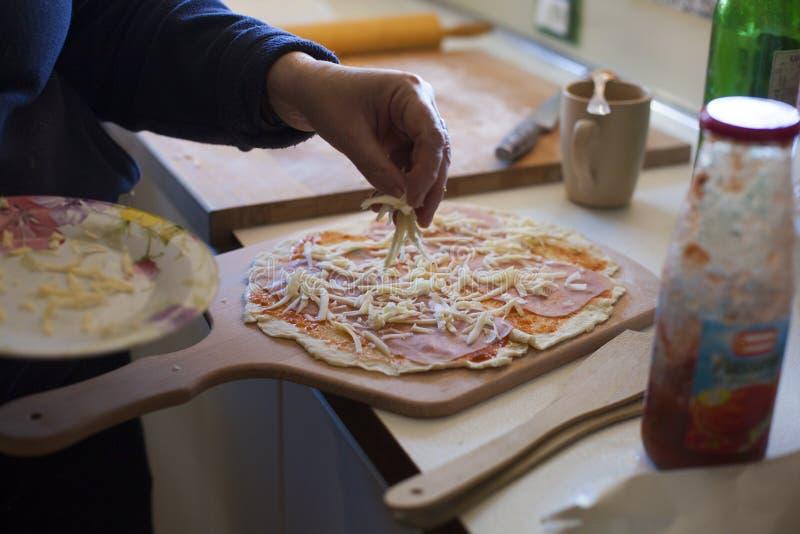 Het zetten van kaas op pizza royalty-vrije stock foto