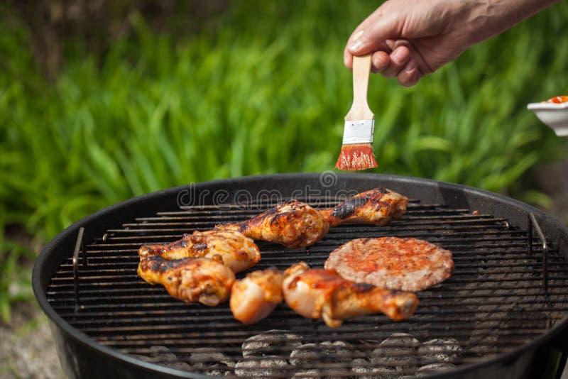 Het zetten van saus op bbq vlees royalty-vrije stock afbeelding