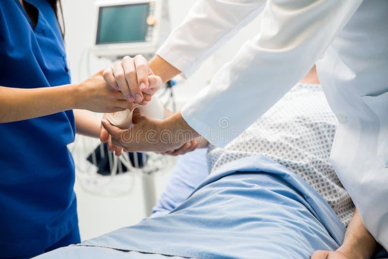 Het zetten van verband op een patiënt stock afbeeldingen