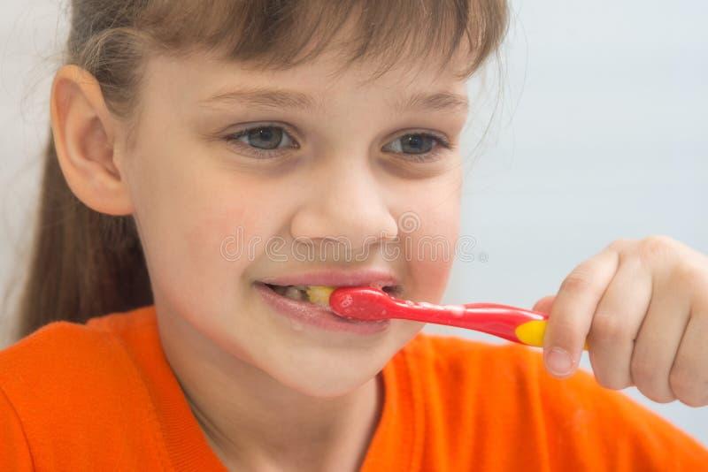 Het zeven-jaar-oude meisje borstelt tanden royalty-vrije stock afbeeldingen