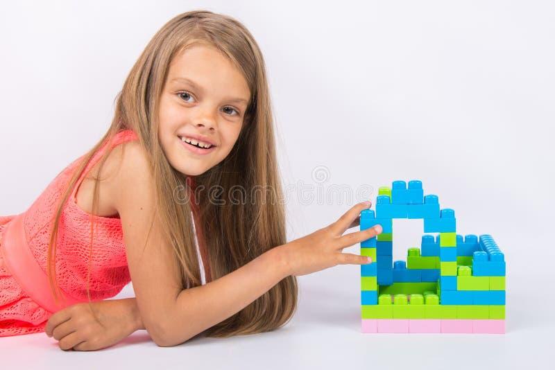 Het zevenjarige meisje heeft een huis van ontwerper kijkt en pret in het kader gebouwd stock fotografie