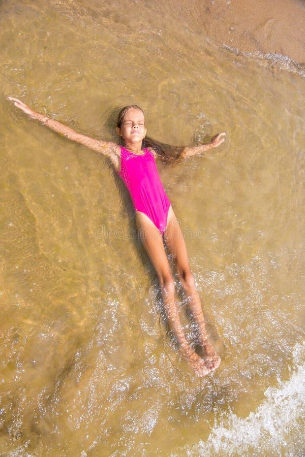 Het zevenjarige meisje ligt terug op haar in water op het zandige strand royalty-vrije stock foto's
