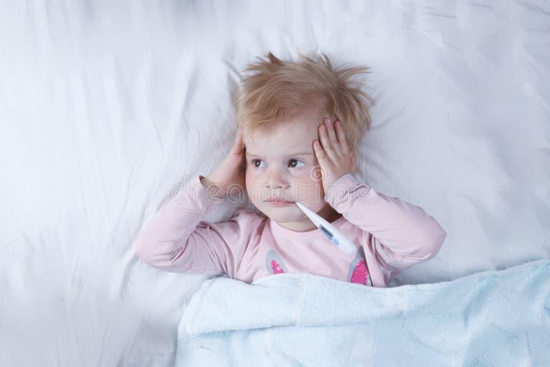 Het zieke meisje, het kind met de thermometer in een mond, op een bed, het concept een ziekte stock afbeelding