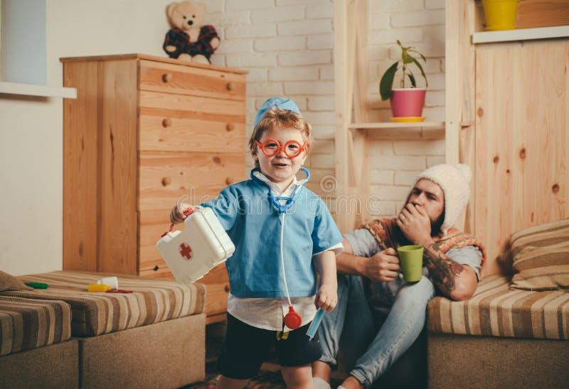 Het het ziekenhuisspel, glimlachende jongen kleedde zich als arts die in rode glazen eerste hulpuitrusting houden Leuk kind met s stock fotografie