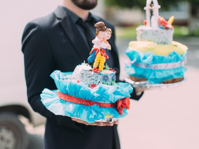 Het zijaanzicht van de huwelijkscake met decoratie door de man worden gedragen die royalty-vrije stock foto