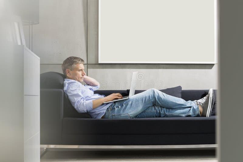 Het zijaanzicht van gemiddelde lengte van de mens die Op middelbare leeftijd laptop met behulp van terwijl het liggen op bank stock afbeeldingen