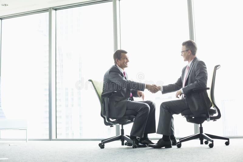 Het zijaanzicht van gemiddelde lengte van zakenlieden die handen schudden terwijl het zitten op bureaustoelen door venster royalty-vrije stock afbeelding
