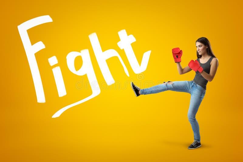 Het zijaanzicht van jong mooi meisje in jeans, sleeveless hoogste en rode bokshandschoenen met been hief voor een schop op geel o stock afbeeldingen