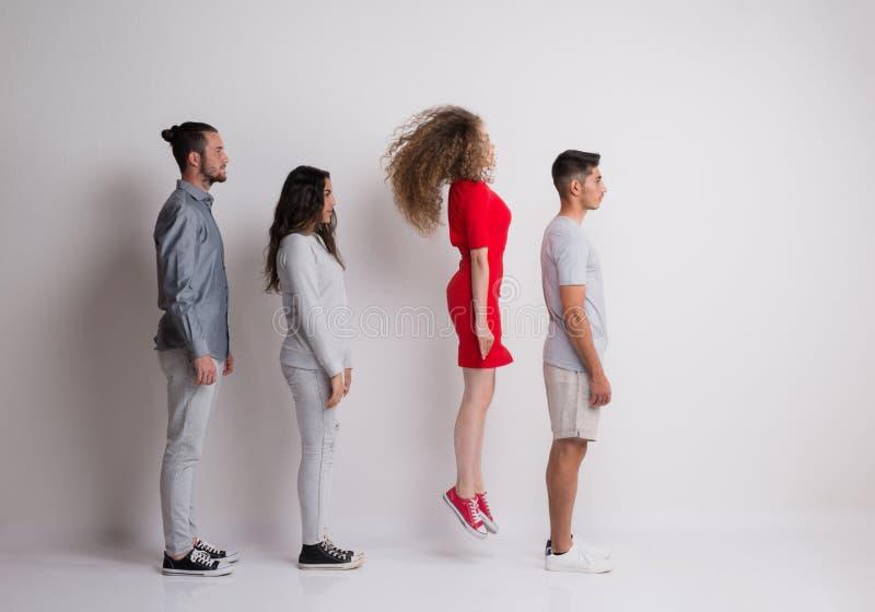 Het zijaanzicht van jonge groep vrienden die zich in een studio, bevinden springt stock foto