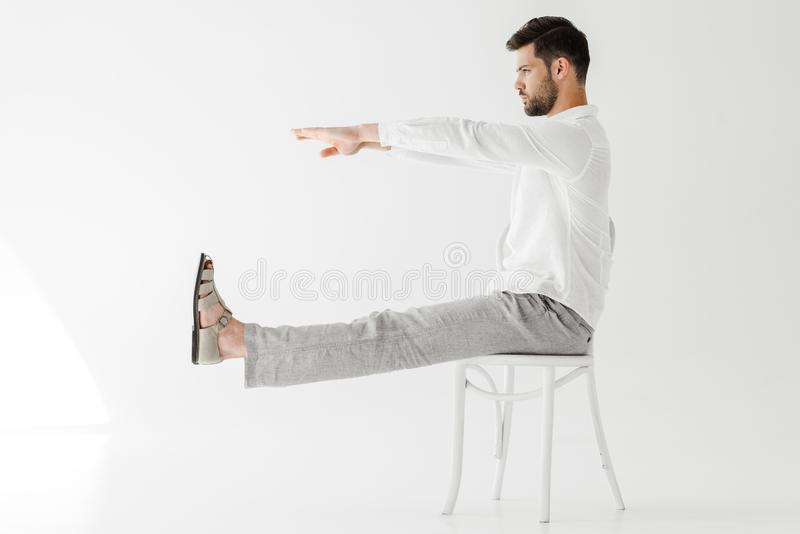 het zijaanzicht van mannelijk model in linnen kleedt het zitten op stoel met uitgestrekte benen en handen stock foto's