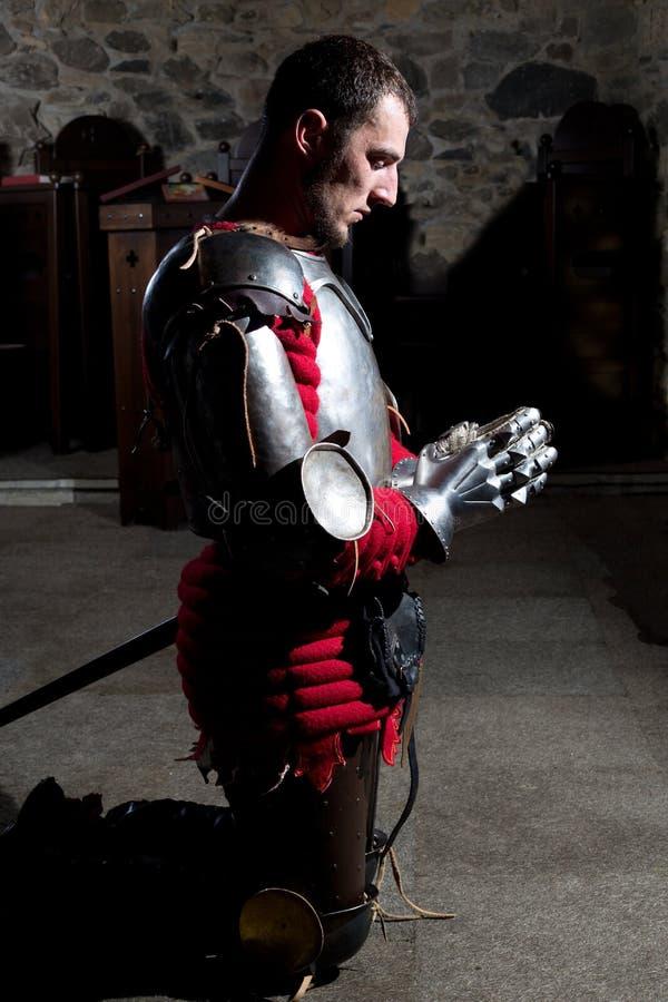 Het Zijaanzicht van Ridder Kneeling op Zijn Knieën met Zijn Hoofd boog en dient Gebed in de Oude Kerk vóór de Slag in stock fotografie