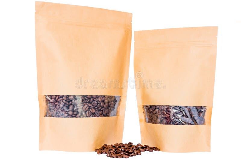 Het zijaanzicht van twee kraftpapier document doypack staat zakken met venster en ritssluiting op met koffiebonen wordt gevuld op royalty-vrije stock afbeeldingen