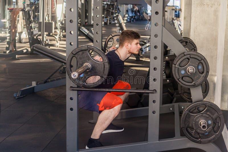 Het zijaanzichtportret van jonge volwassen bodybuilder is training in gymnastiek die alleen en aan het opheffen prepearing barbel royalty-vrije stock foto's