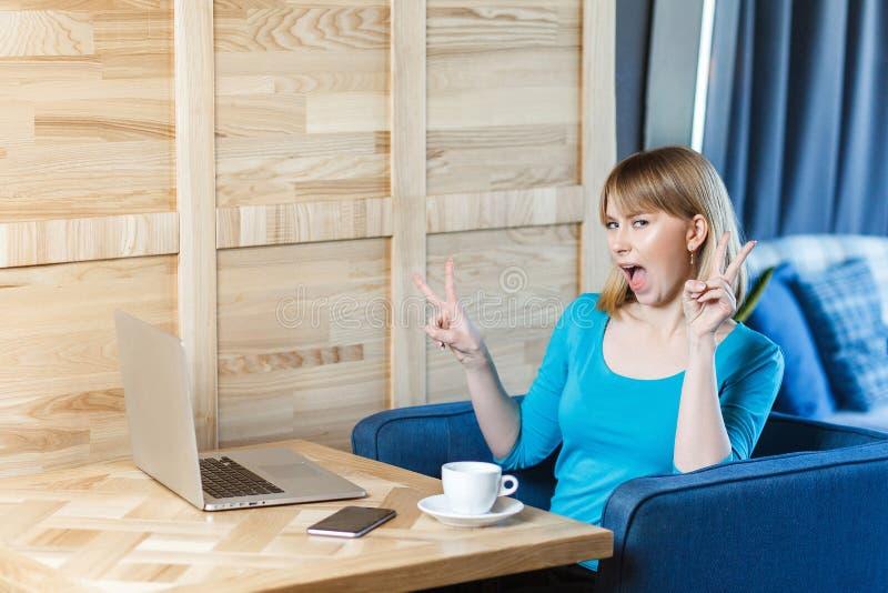 Het zijaanzichtportret van mooi emotioneel positief meisje met blondehaar in blauwe blouse zit in koffie en werkt aan laptop royalty-vrije stock foto