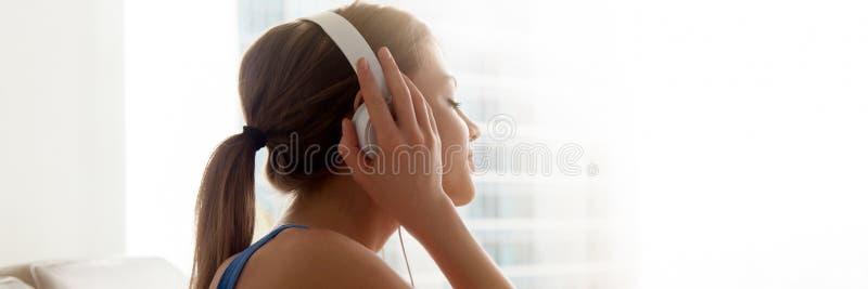 Het zijaanzichtwijfje die hoofdtelefoons dragen geniet thuis van favoriete muziek royalty-vrije stock foto's