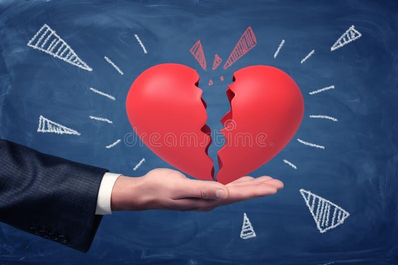 Het zijgewassenclose-up die van man hand omhoog en groot rood hart onder ogen zien houden verdeelde in de helften op bordachtergr stock fotografie